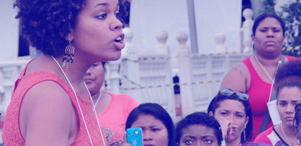 Mulher discursa para plateia feminina durante encontro nacional de mulheres