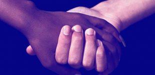 Mãos dadas entre uma pessoa negra e outra branca